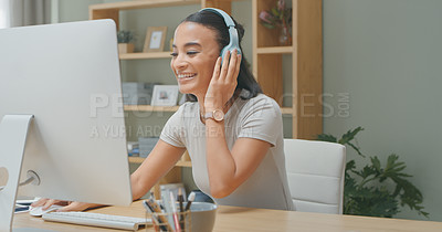 Buy stock photo Shot of a young woman using a computer while wearing headphones at home