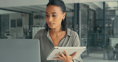 Buy stock photo Shot of a young woman using her digital tablet and laptop to get her work done in a modern office