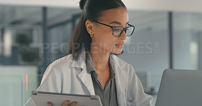 Buy stock photo Shot of a young female doctor using her digital tablet in her office