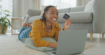 Buy stock photo Shot of a young woman holding a credit card while using a computer at home