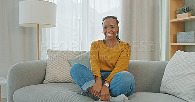 Buy stock photo Portrait shot of a young woman sitting on the couch at home