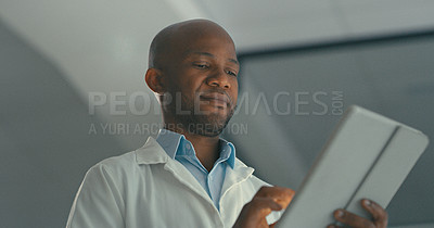 Buy stock photo Shot of a young male doctor using his digital tablet in his office
