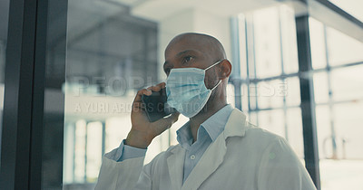 Buy stock photo Shot of a young male doctor using his smartphone to make a phone call
