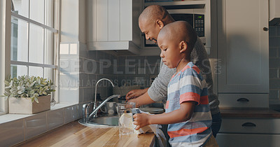 Buy stock photo Shot of a mature man and his grandson doing the dishes at home