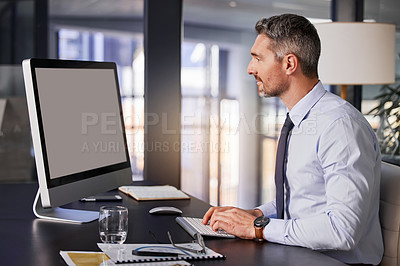 Buy stock photo Shot of a businessman using his computer while sitting at his desk