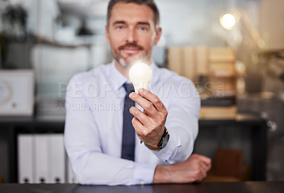 Buy stock photo Shot of a businessman holding a lightbulb while sitting at his desk