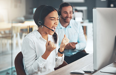Buy stock photo Shot of a young call centre agent sitting with a colleague in her office and celebrating a success