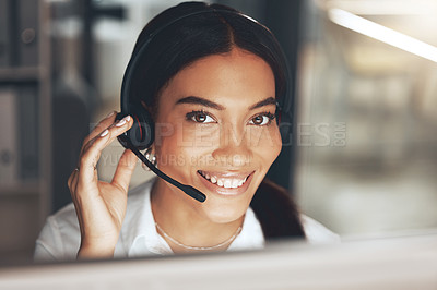 Buy stock photo Shot of a young call centre agent sitting alone in her office and using her computer
