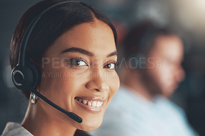 Buy stock photo Shot of a young call centre agent sitting in the office with her colleague