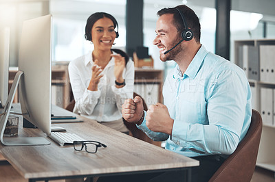 Buy stock photo Shot of a young call centre agent sitting with a colleague in his office and celebrating a success