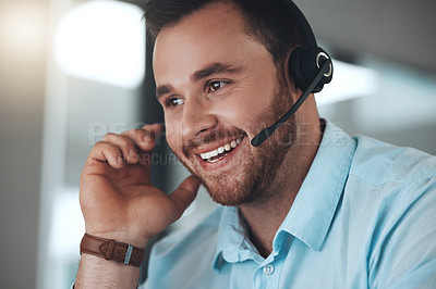 Buy stock photo Shot of a young call centre agent sitting alone in his office and using his computer
