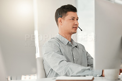 Buy stock photo Shot of a young male call center agent using a computer in an office at work