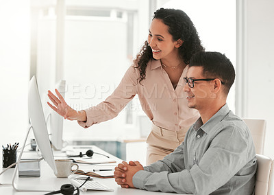 Buy stock photo Shot of two young colleagues using a computer in an office at work