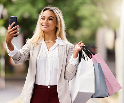 Buy stock photo Cropped shot of an attractive young woman taking selfies while out shopping in the city