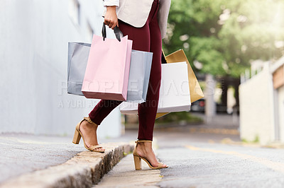 Buy stock photo Cropped shot of an unrecognizable young woman crossing the street while out shopping in the city