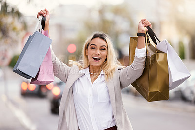 Buy stock photo Cropped portrait of an attractive young woman raising her bags after a successful day of shopping in the city