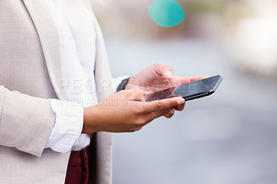 Buy stock photo Cropped shot of an unrecognizable young businesswoman texting while walking through the city