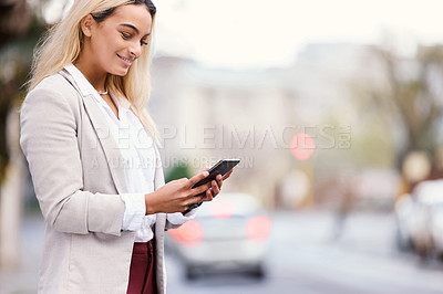 Buy stock photo Cropped shot of an attractive young businesswoman texting while walking through the city