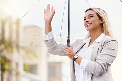 Buy stock photo Cropped shot of an attractive young businesswoman waving while walking through the city with an umbrella