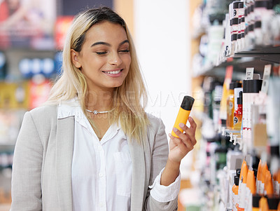 Buy stock photo Cropped shot of an attractive young woman shopping in a cosmetics store