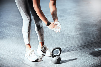 Buy stock photo Cropped shot of an unrecognizable woman lifting a kettlebell at the gym
