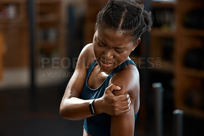 Buy stock photo High angle shot of an attractive and athletic young woman holding her shoulder in pain while at the gym