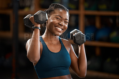Buy stock photo Cropped portrait of an attractive and athletic young woman working out with dumbbells in the gym
