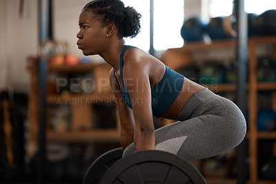 Buy stock photo Cropped shot of an attractive and athletic young woman working out with a barbell in the gym