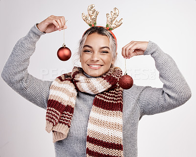 Buy stock photo Studio portrait of an attractive young woman holding up baubles while dressed in Christmas-themed attire