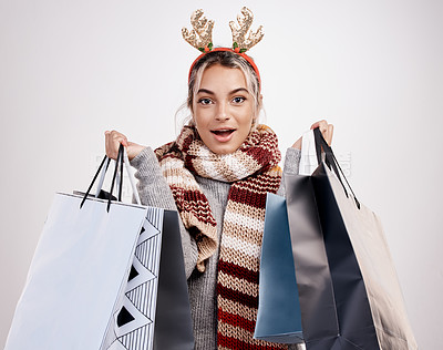 Buy stock photo Studio portrait of an attractive young woman holding a bunch of gift bags while dressed in Christmas-themed attire