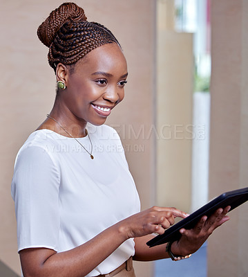 Buy stock photo Shot of a young woman using a digital tablet in a modern office