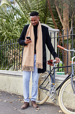 Buy stock photo Shot of a young business man using his cellphone outside
