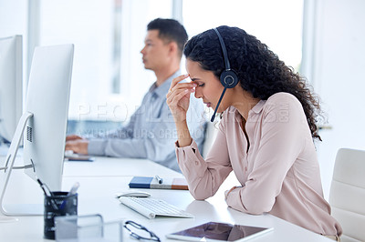 Buy stock photo Shot of a young call centre agent sitting with her colleague and feeling stressed while using her computer