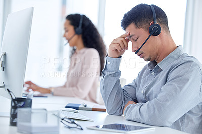 Buy stock photo Shot of a young call centre agent sitting with his colleague and feeling stressed while using his computer