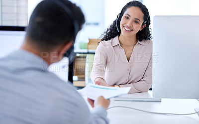 Buy stock photo Shot of a young call centre agent sitting and working with a colleague in the office