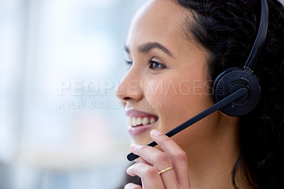 Buy stock photo Shot of an attractive young call centre agent sitting alone in her office during the day