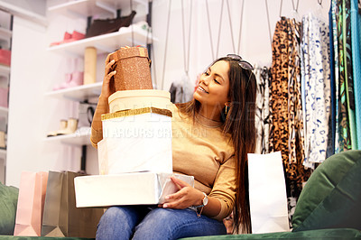 Buy stock photo Shot of a young woman sitting in a store with gift boxes stacked on her lap