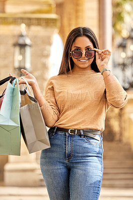 Buy stock photo Cropped portrait of an attractive young woman carrying a bunch of bags while shopping in the city