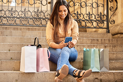 Buy stock photo Full length shot of an attractive young woman taking a break from shopping to send a text message