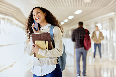 Buy stock photo Cropped shot of an attractive young female student making a call while standing in a campus hallway