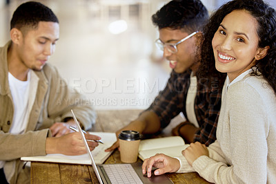 Buy stock photo Cropped portrait of an attractive young female college student studying in the library with two male classmates