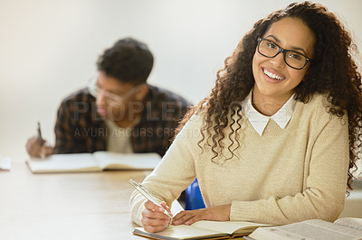 Buy stock photo Cropped portrait of an attractive young female college student writing in her notebook while sitting in class