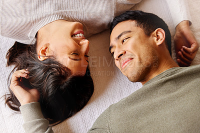 Buy stock photo Shot of a young couple laying on the floor at home