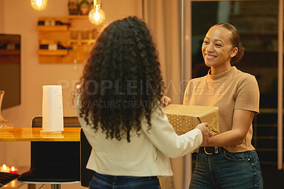 Buy stock photo Shot of a young woman giving her friend a birthday gift