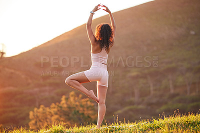 Buy stock photo Rearview shot of an unrecognizable young woman practicing yoga outside on a sunny morning