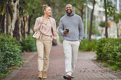 Buy stock photo Full length shot of two corporate businesspeople chatting while walking through the city