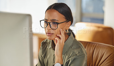 Buy stock photo Shot of a young businesswoman looking confused while working on a computer in an office
