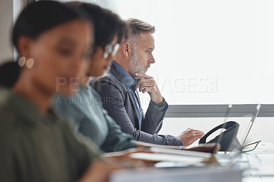 Buy stock photo Shot of a mature businessman working on a laptop alongside his colleagues in a call centre