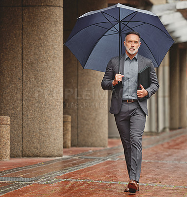 Buy stock photo Shot of a handsome businessman walking to work on a rainy day