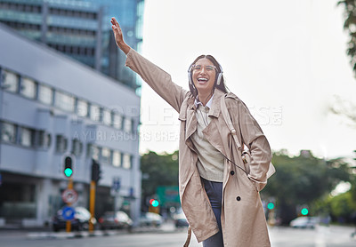 Buy stock photo Shot of a young businesswoman hailing a cab in town